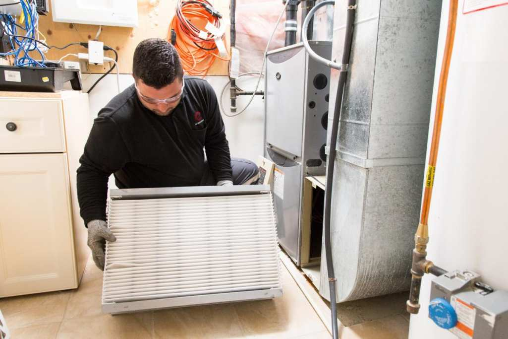 Enercare technician inspecting furnace filter