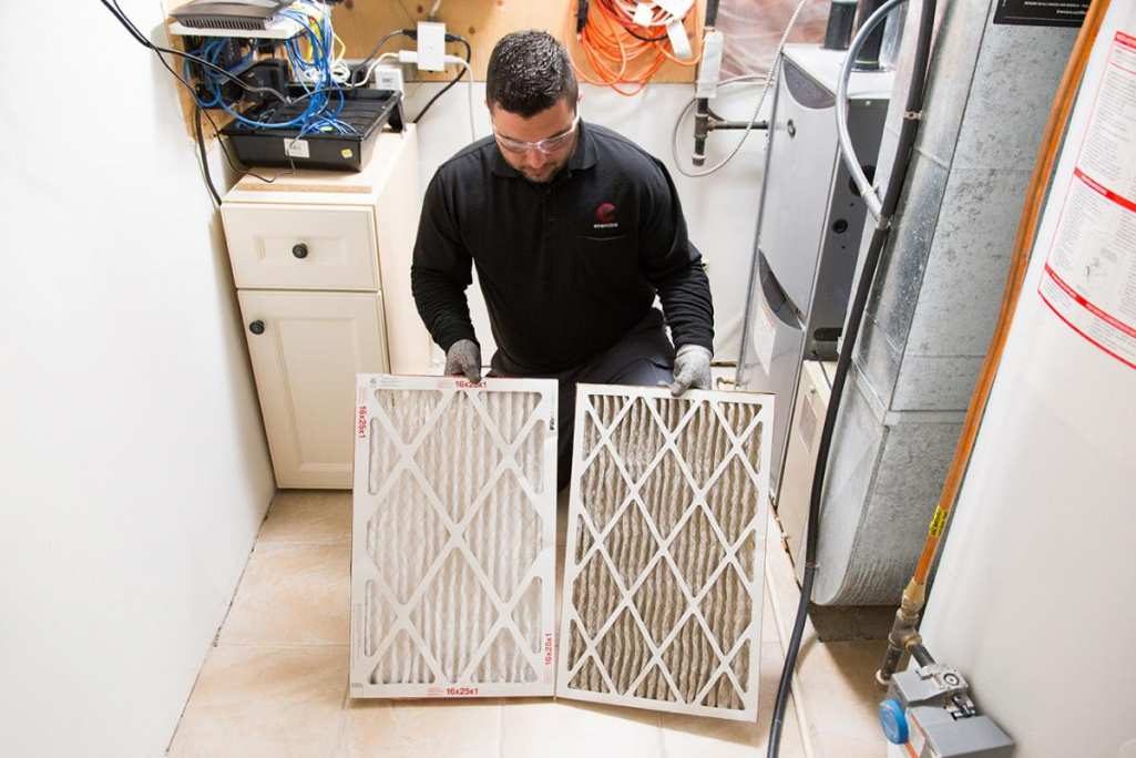 Enercare technician comparing two furnace filters