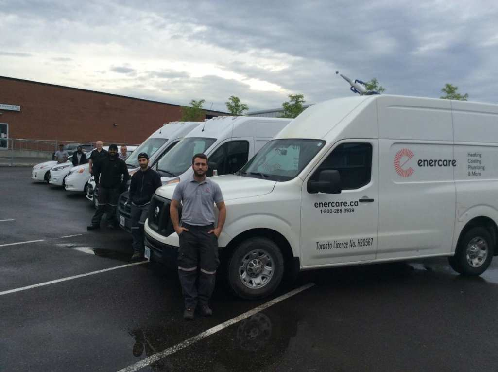 Enercare employees standing in front of service vans