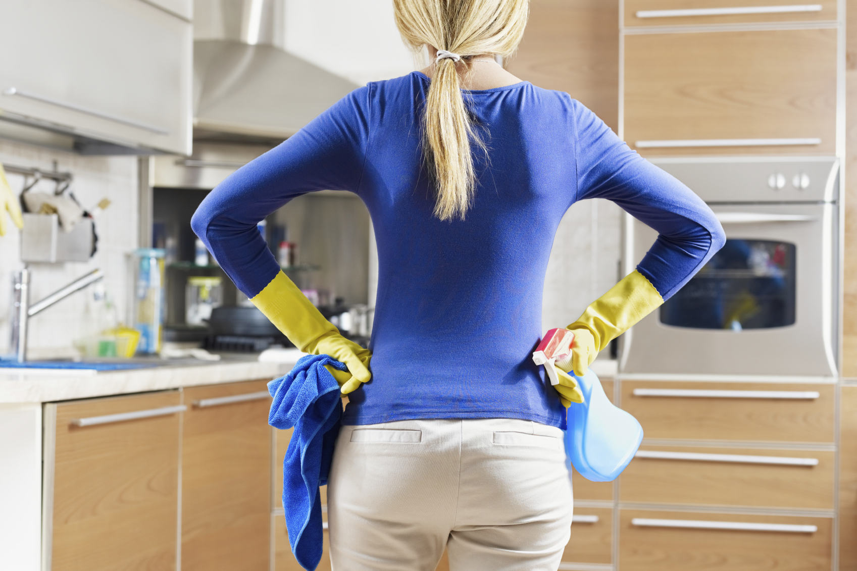 Woman with hands on hips holding cleaning supplies